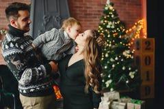 Gullig familj som sitter nära julgranen arkivfoto