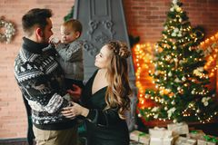Gullig familj som sitter nära julgranen royaltyfria bilder