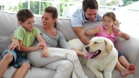 Gullig familj som tillsammans kopplar av på soffan med deras hund arkivfilmer