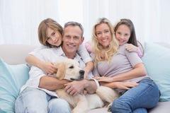 Gullig familj som tillsammans kopplar av på soffan med deras hund arkivbilder
