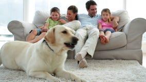 Gullig familj som tillsammans kopplar av på soffan med deras hund på filten