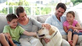 Gullig familj som tillsammans kopplar av på soffan med deras labrador hund