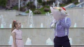 Gullig fars i röd basker ger buketten av blommor till lite flickan arkivfilmer