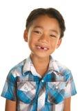 Gullig filippinsk pojke på vit bakgrund som ler med miss av Front Teeth Royaltyfri Foto