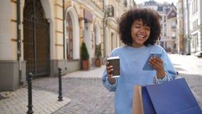 Gullig flicka för blandat lopp som är upptagen med mobiltelefonen på gatan stock video