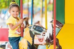 Gullig flicka för blandat lopp som rider en karusell Royaltyfria Bilder
