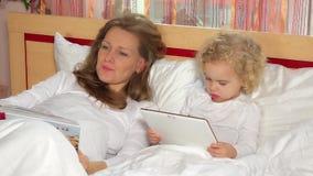 Gullig flicka för litet barn med minnestavladatoren och hennes unga moderläsebok lager videofilmer