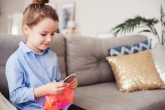Gullig flicka för litet barn med spegeln och den kosmetiska påsen som hemma kontrollerar frisyren royaltyfri bild