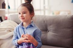 Gullig flicka för litet barn med spegeln och den kosmetiska påsen som hemma kontrollerar frisyren Royaltyfria Bilder