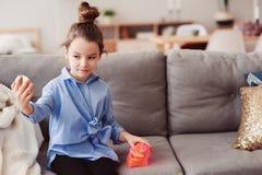 Gullig flicka för litet barn med spegeln och den kosmetiska påsen som hemma kontrollerar frisyren royaltyfri foto