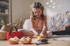 Gullig flicka för litet barn som hemma spelar i hennes rum med leksakmat, matlagning och har gyckel Royaltyfri Foto