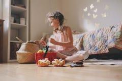 Gullig flicka för litet barn som hemma spelar i hennes rum med leksakmat, matlagning och har gyckel Arkivbild