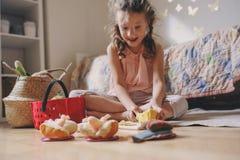 Gullig flicka för litet barn som hemma spelar i hennes rum med leksakmat, matlagning och har gyckel Royaltyfria Bilder