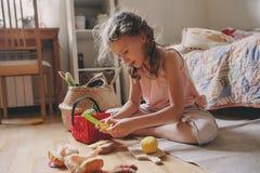 Gullig flicka för litet barn som hemma spelar i hennes rum med leksakmat, matlagning och har gyckel Royaltyfria Foton