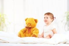 Gullig flicka för litet barn som kramar nallebjörnen i säng Arkivfoto