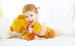Gullig flicka för litet barn som kramar nallebjörnen i säng royaltyfri fotografi