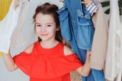 gullig flicka för litet barn som väljer ny modern kläder i hennes garderob- eller lagerprovhytt royaltyfri bild