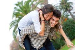 gullig flicka för pojkvän som piggybacking Arkivbilder