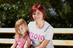 gullig flicka henne liten mom utomhus Fotografering för Bildbyråer