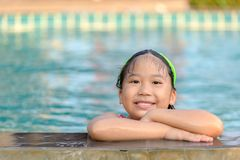 Gullig flicka i bad för en baddräkt i pölen royaltyfri foto