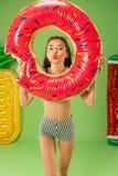 Gullig flicka i baddräkten som poserar på studion Caucasian tonåring för sommarstående på grön bakgrund Royaltyfri Fotografi