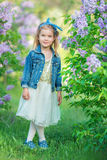 Gullig flicka i blåa omslag med den felika luftiga kjolen som nästan står den lila busken Arkivfoto