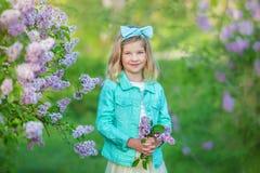 Gullig flicka i blåa omslag med den felika luftiga kjolen som nästan står den lila busken Royaltyfri Foto