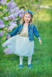 Gullig flicka i blåa omslag med den felika luftiga kjolen som nästan står den lila busken Arkivbild