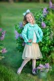 Gullig flicka i blåa omslag med den felika luftiga kjolen som nästan står den lila busken Arkivbilder