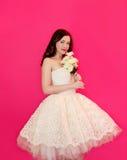 Gullig flicka i blommor för ett bröllopsklänninginnehav Arkivfoton
