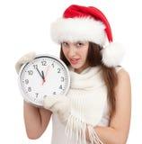 Gullig flicka i den röda santa för jul hatten med klockan arkivfoton