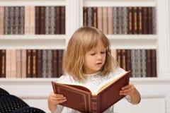 Gullig flicka i den vita läseboken i arkiv royaltyfri fotografi