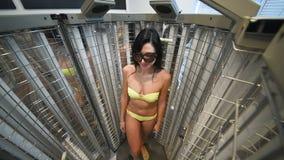 Gullig flicka i en baddräkt i en special kabin med UV lampor för behandlingen av psoriasins arkivfilmer