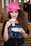 Gullig flicka i ett sammanträde för vagndrev och ett drickakaffe eller te Royaltyfri Foto