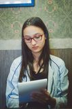 Gullig flicka i exponeringsglas som rymmer en notepad i hennes händer arkivbilder