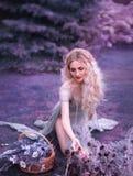 Gullig flicka i gammal grå klänning med det långa klippta drevet och öppna ben som sitter på knä och samlar lösa blommor som är m royaltyfria foton