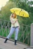 Gullig flicka i gul skjorta och jeans som går på bron med ett ljust paraply på aftonen arkivfoton