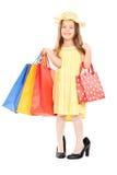 Gullig flicka i hållande shoppingpåsar för maskeradkläder Arkivbilder