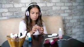 Gullig flicka i hörlurar som sjunger lyssnande musik på telefonen, medan göra manikyr hem- utrymme för fri kopia lager videofilmer