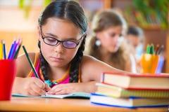 Gullig flicka i klassrum på skolan Arkivfoto