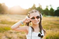 Gullig flicka i lyssnande musik för solglasögon Arkivbild