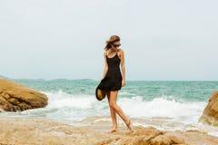 Gullig flicka i svart sommarklänning på stora stenar Fotografering för Bildbyråer