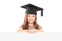 Gullig flicka med avläggande av examenhatten som poserar bak panel Royaltyfri Fotografi