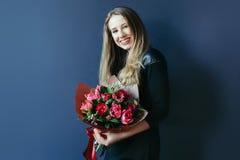 Gullig flicka med buketten av röda tulpan arkivbilder