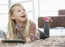 Gullig flicka med den digitala minnestavlan som ser bort, medan ligga på filten i vardagsrum Fotografering för Bildbyråer