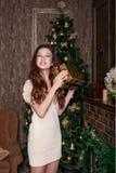 Gullig flicka med en julgåva i händer i lyckligt anseende för fröjd i vardagsrummet av en klassisk stil i en guld- retro vintag royaltyfri fotografi