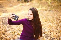 Gullig flicka med en smartphone i höstskogen royaltyfria bilder