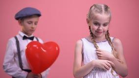 Gullig flicka med flätade trådar som ler till kameran med den blyga pojken i bakgrund, första förälskelse stock video