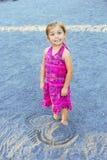 Gullig flicka med fot som begravas i sand royaltyfria foton