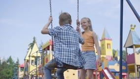 Gullig flicka med långt hår som utomhus svänger på en gullig pojke för gunga Par av lyckliga barn Förälskade roliga bekymmerslösa lager videofilmer